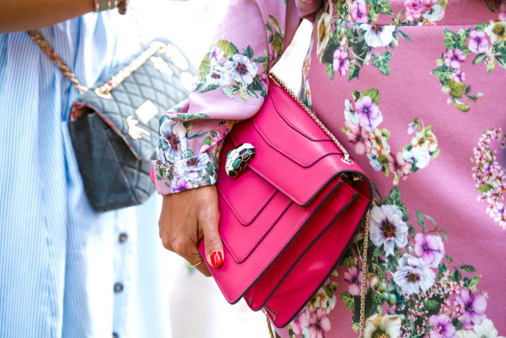 women holding pink and blue designer handbags bvlgari and chanel